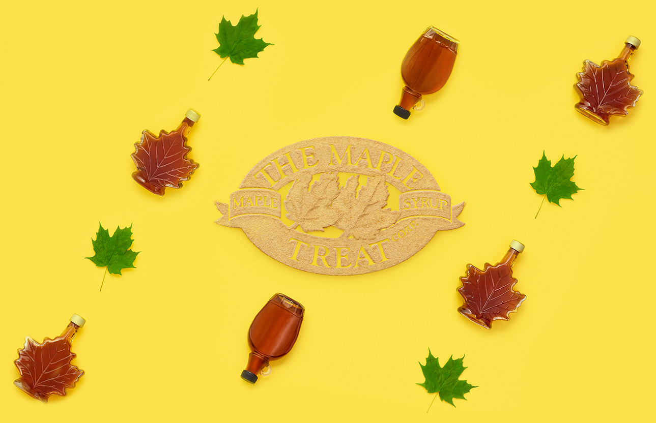 The Maple Treat logo Corp. made with maple sugar, with bottles of maple syrup and maple leaves surrounding it.
