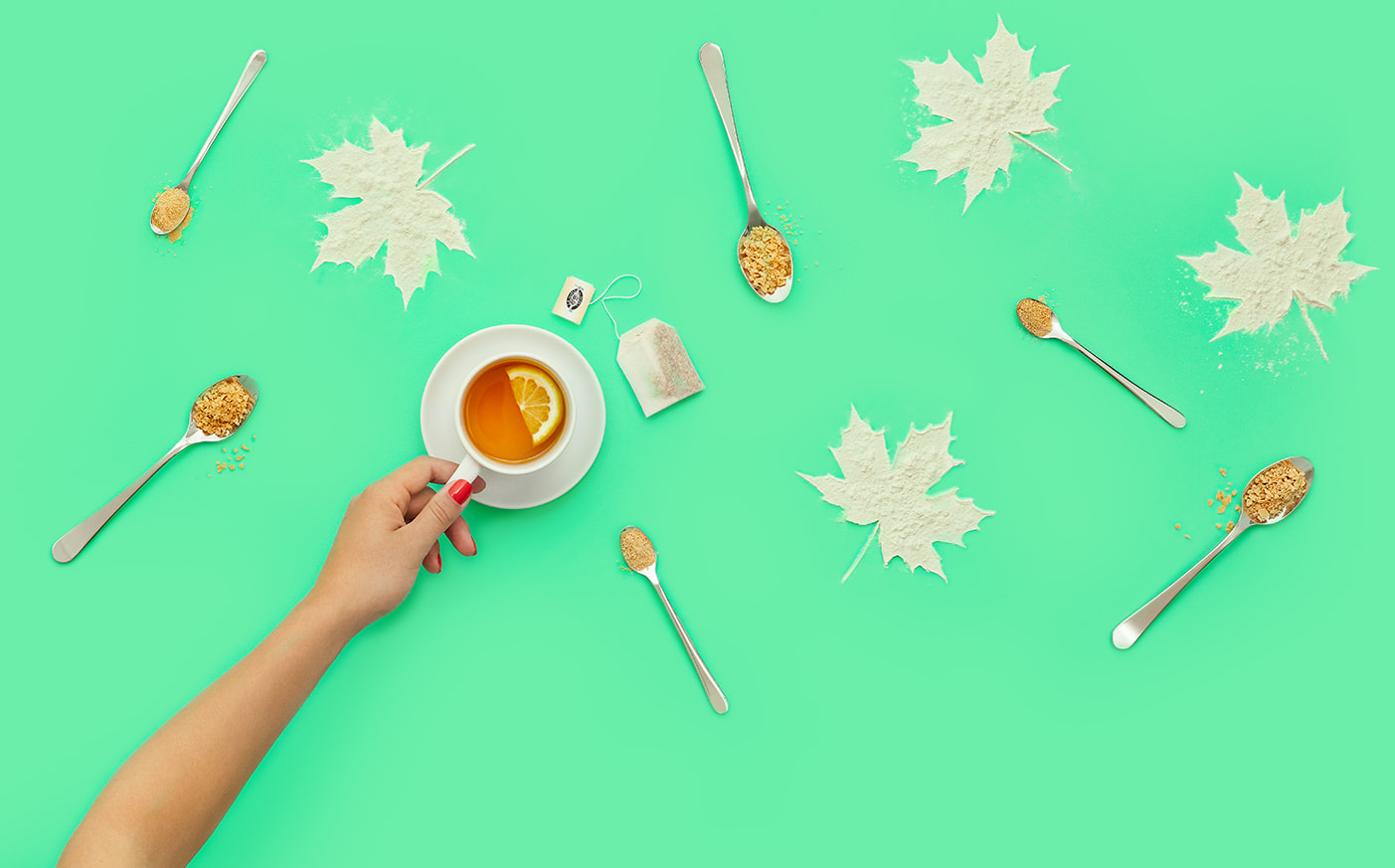Cup of maple tea with lemon wedge beside spoons with maple flakes.