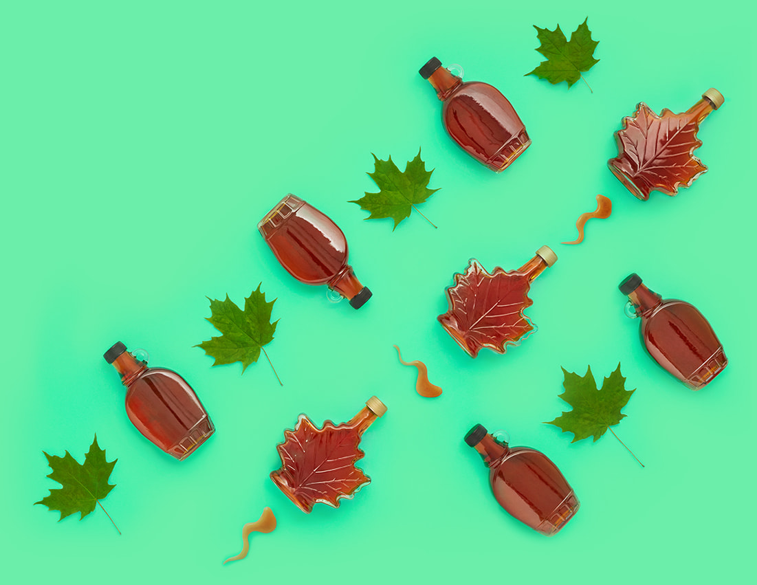 Green background with decorative glass maple syrup bottles arranged in a pattern with green maples leaves.