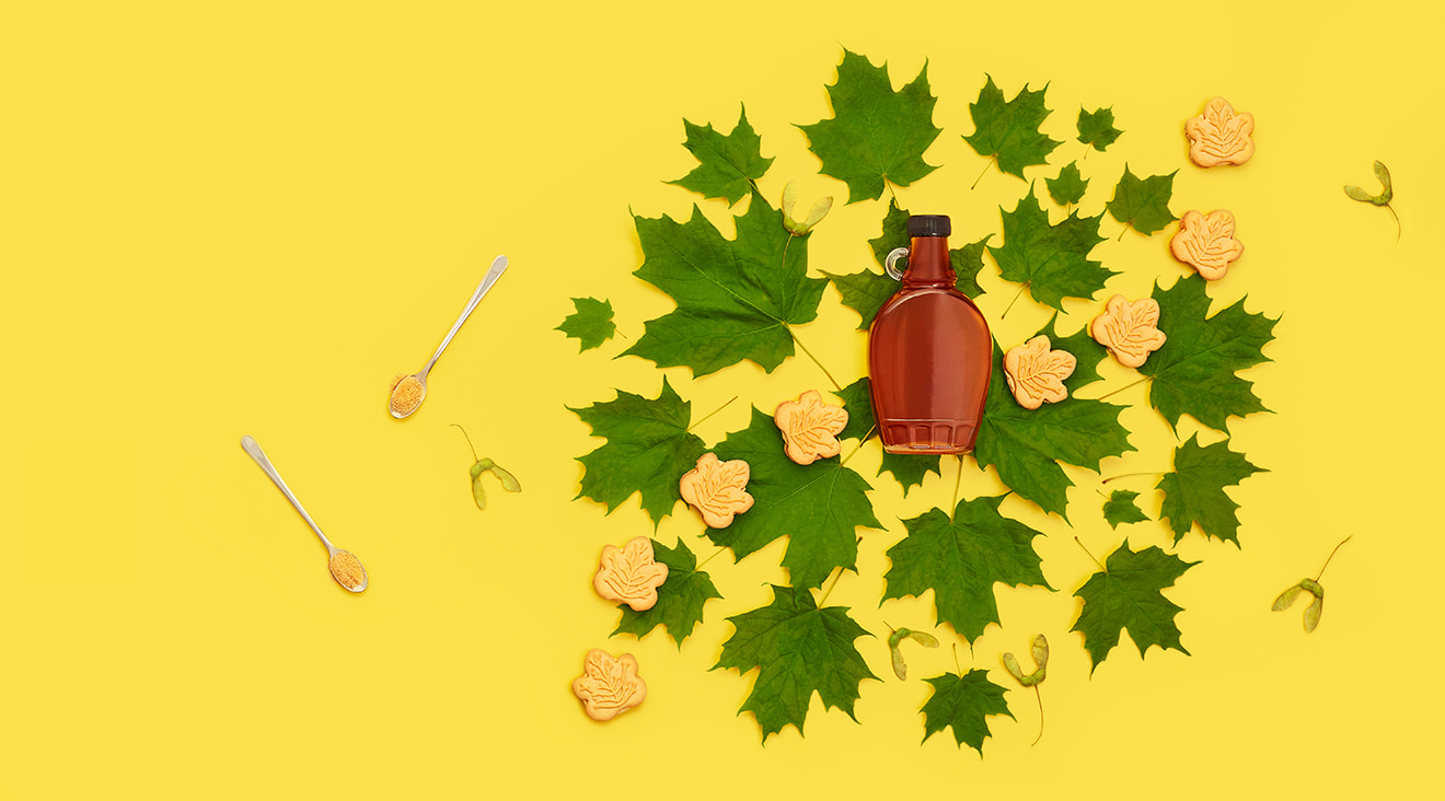 Maple syrup bottle surrounded by green maple leaves, maple cookies, and spoons filled with maple flakes.