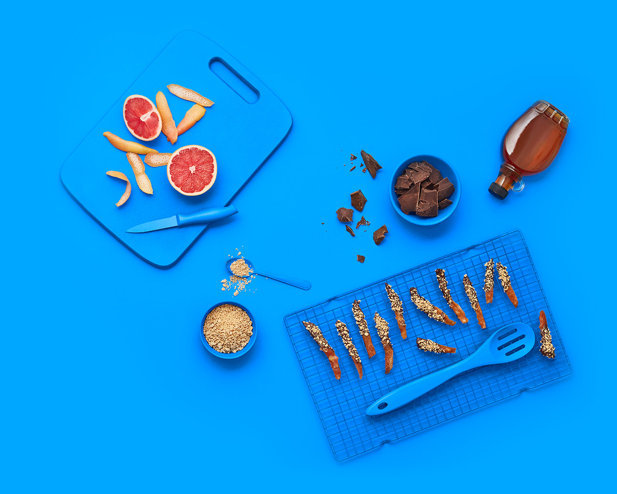 Blue background with candied fruit peels, and a bowl and spoon with maple flakes.
