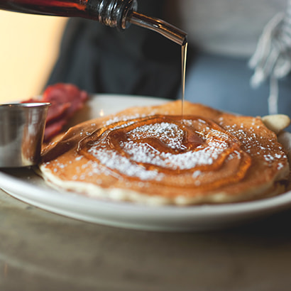 Pancakes with icing sugar and maple syrup being poured on top.